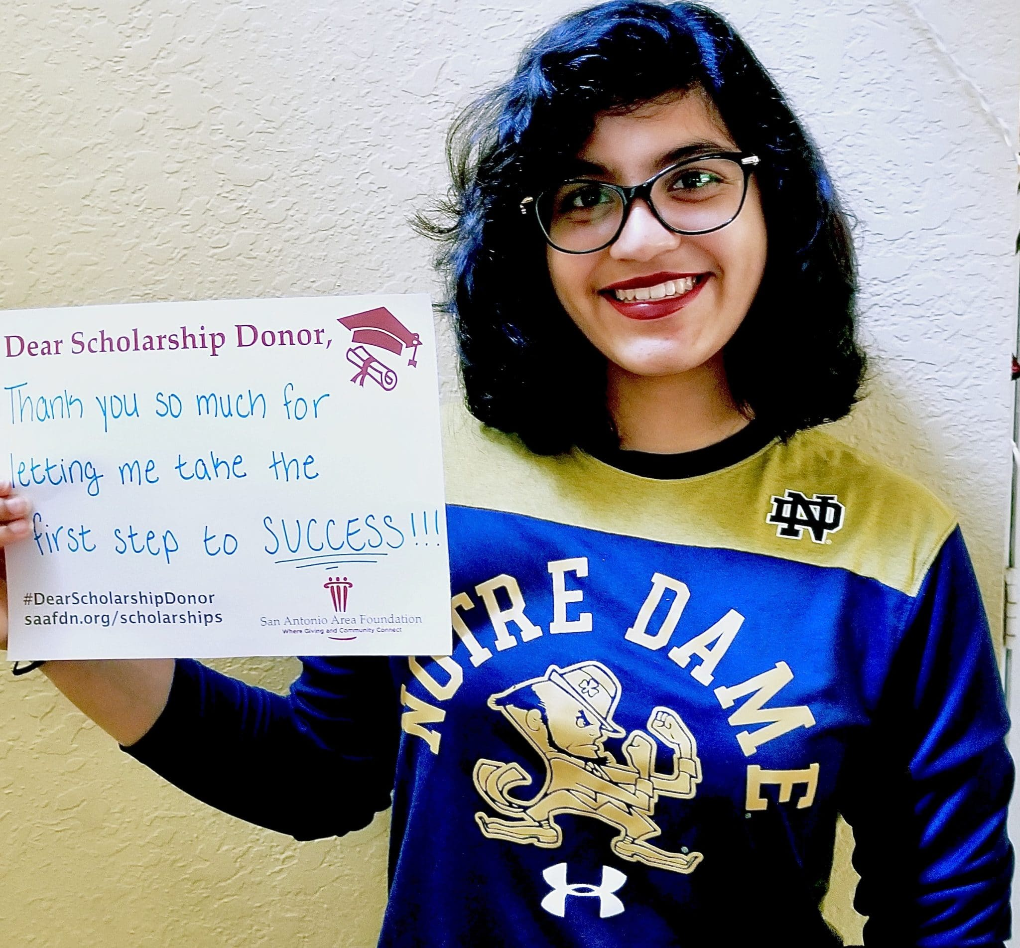 Scholarship recipient holding a thank you sign