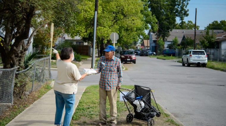 Mari Lopez, left, hands a free lunch to a walk-up at House of Neighborly Services Wednesday, Sept. 16, 2020. HNS is using extra safety protocols for the safe handling and delivery of food to needy neighbors.