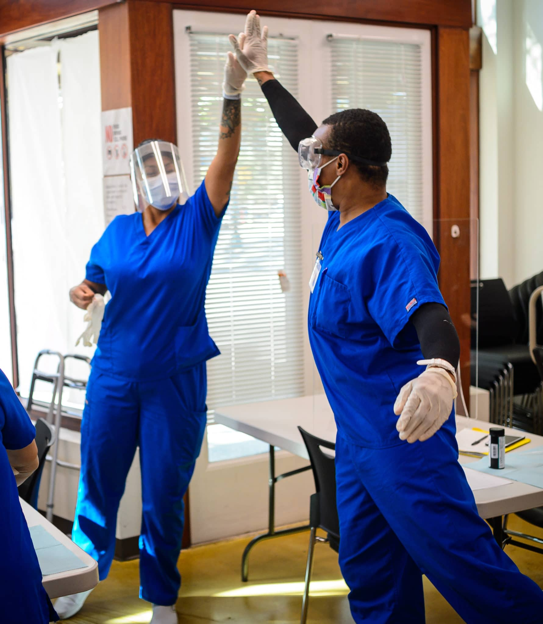Medical Assistant students Amanda DeLaO, left, and Terence Flowers high-five at Goodwill's Good Careers Academy