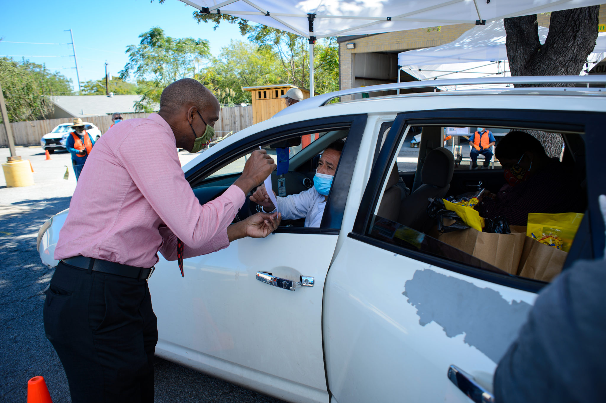 Bobby Blount hands out census information to a family who stopped for groceries at the Antioch Missionary Baptist Church food pantry and census drive